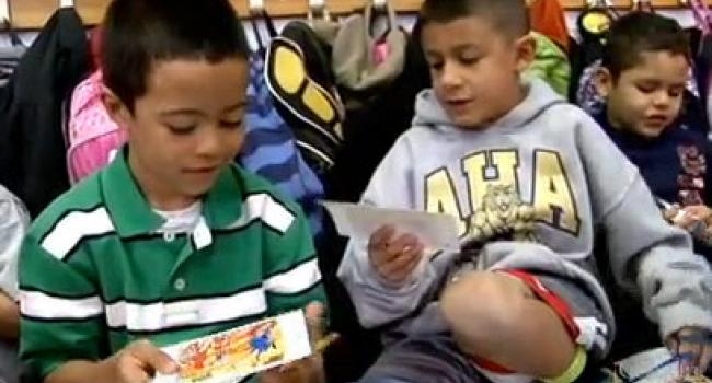 two young kids holding square pieces of paper in their hands