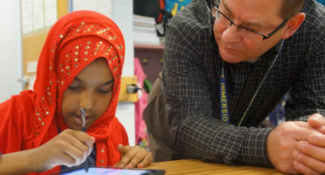 A man helping a girl in a hijab with her schoolwork.