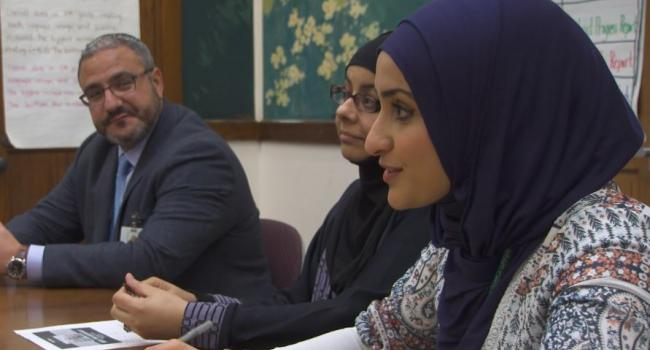 three people sitting at a table. one woman is in a hijab.