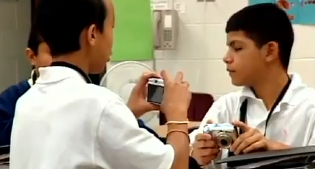three boys playing with digital cameras