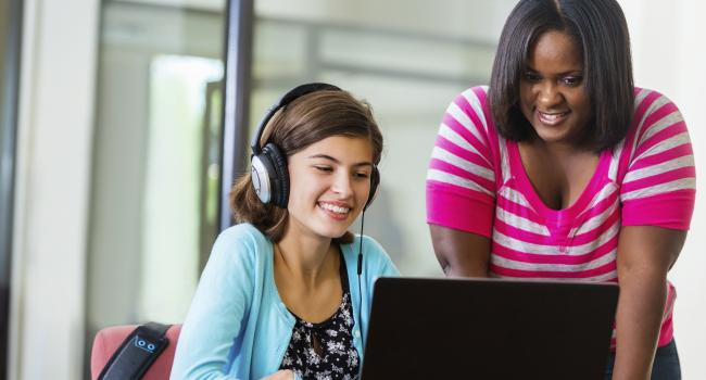 two young women looking at a laptop screen and one has on headphones