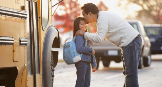 man kissing girl on the forehead before she gets on the school bus