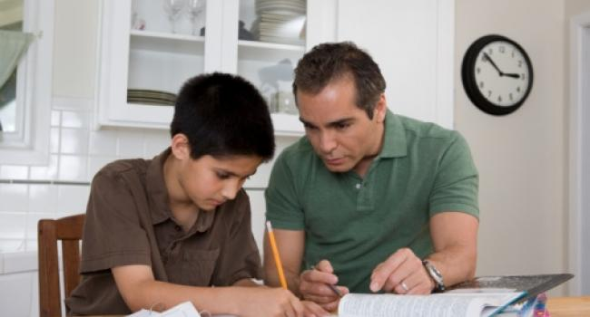 a man and a boy sitting at the kitchen table working on homework