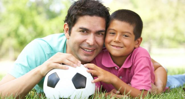 boy and man laying in the grass holding a soccer ball