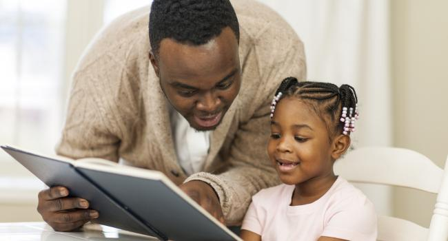 A man helping a young girl read
