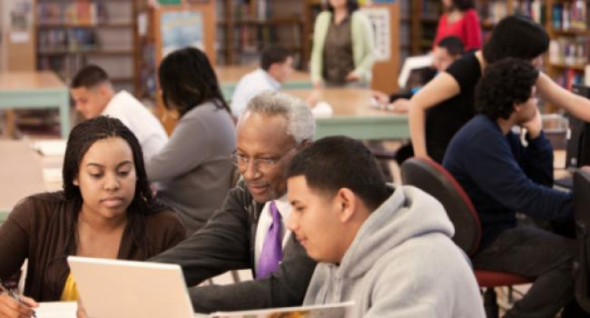 a man looking at a laptop with two young adults in the library