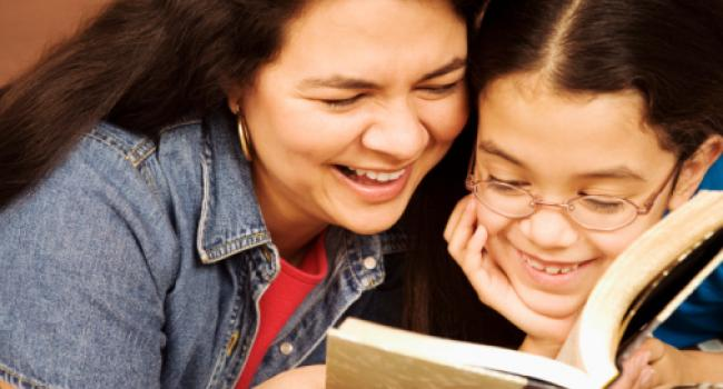 an adult and a child smiling as they read a book