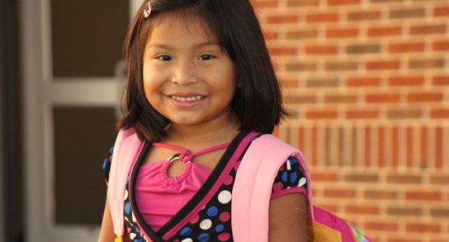 young girl smiling at camera and wearing a backpack