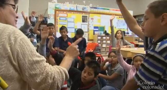 a group of children in a classroom all raising their hands