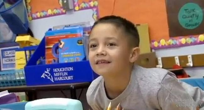 A young boy in a classroom smiling at something off-camera
