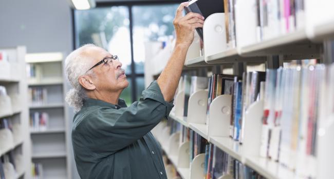 man putting book on a bookshelf