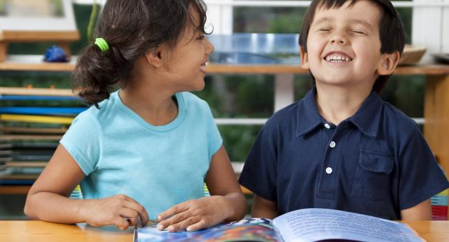 two kids laughing with a book on the table in front of them