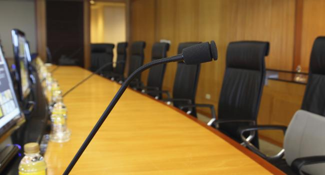 microphones and empty chairs at a conference table