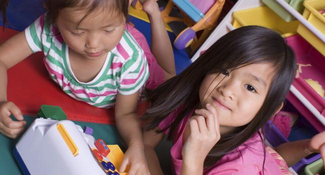 two girls laying on a classroom floor playing with toy