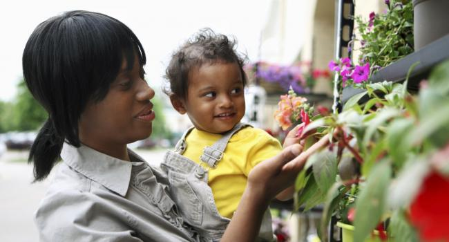 woman holding a child and both are looking at plants