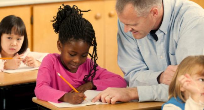 man helping young girl as she writes