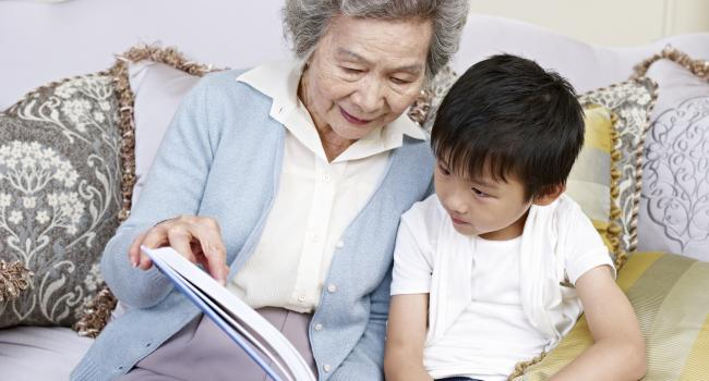 an older woman reading a book to a young child while sitting on a couch