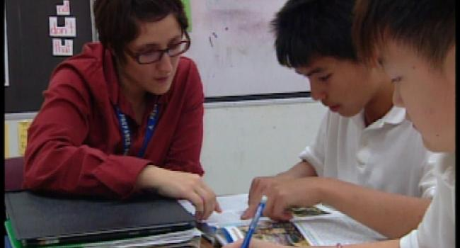 a teacher helping two young students with their reading