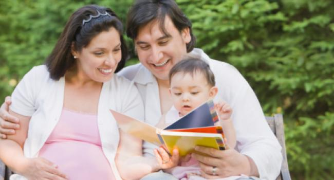 A pregnant woman, a man, and a baby all looking at a book