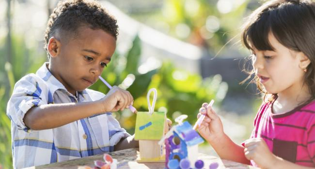 a boy and a girl painting small birdhouses