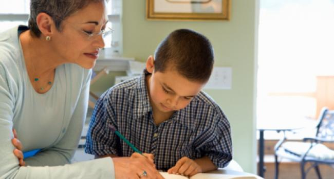 woman working with boy on writing