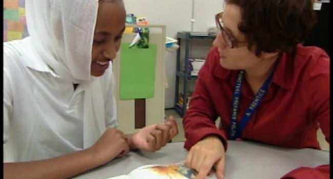 teacher helping young girl in hijab with reading