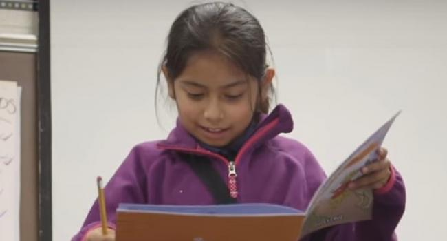 Student reading out loud from book