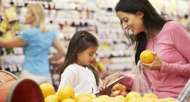 woman looking at ornages with a child in the supermarket