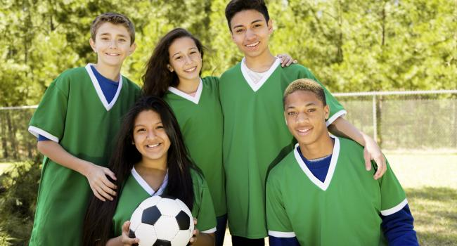 five young adults in uniforms and one is holding a soccer ball