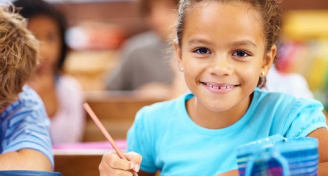 A girl smiling into the camera with a pencil in her hand.