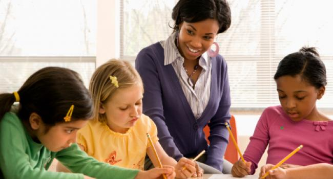 A woman smiling at three young girls who are writing.