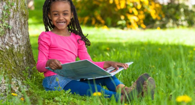 A girl sitting in the grass with a book and smiling at the camera.