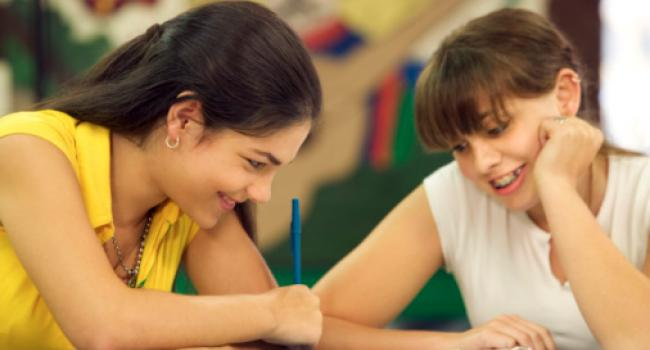 Two smiling young adults looking at what one of them is writing.