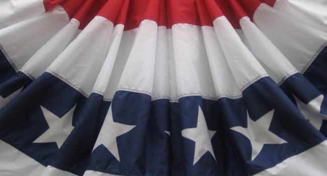 A fan of cloth decorated in red, white, and blue bands with stars on the blue.