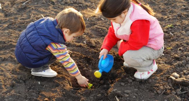 A boy and girl digging in the dirt.