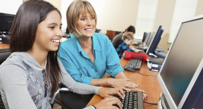 A smiling woman sitting next to a smiling girl who is working on the computer.