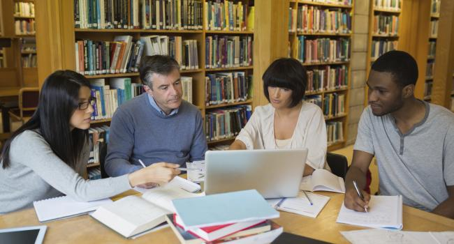 Four adults sitting at a library table looking at a laptop.