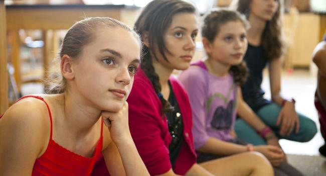 Four girls listening to someone off camera.