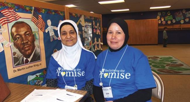 Two women in hijab sitting at a table and smiling at the camera.