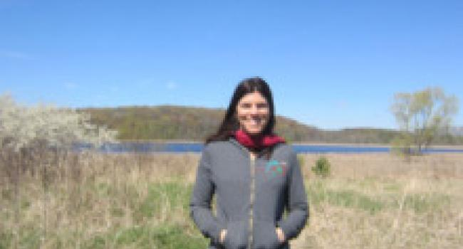 a woman standing in front of a lake and smiling at the camera