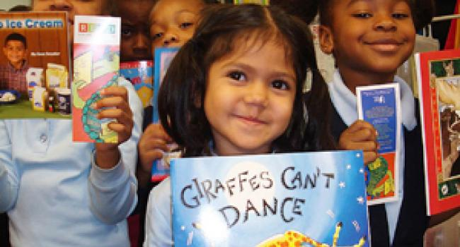 Smiling children holding up books in front of them.