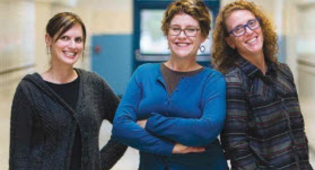 Three smiling women in a hallway.