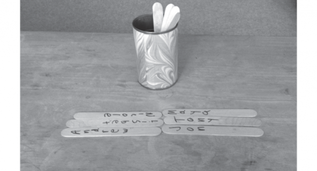 A black and white photo of a cup of popsicle sticks on a table and six are laid out.