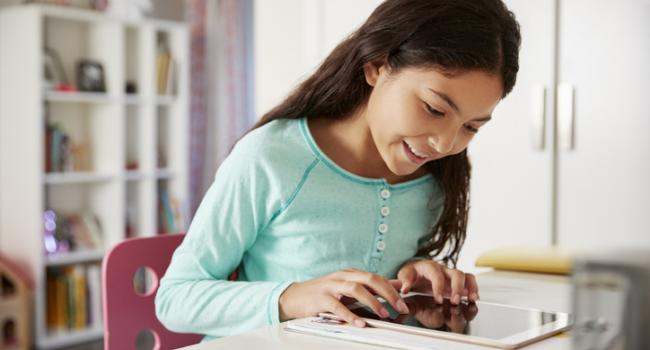 Girl working on tablet in room
