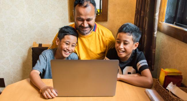 Brothers with tablet and laptop at home