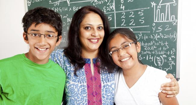 A woman and two children are smiling at the camera