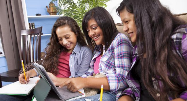 Three girls smiling as they do work on a tablet computer