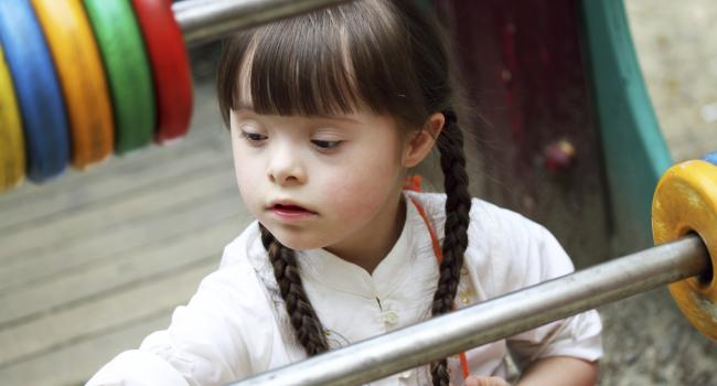 A young girl with Down Syndrome playing on the playground
