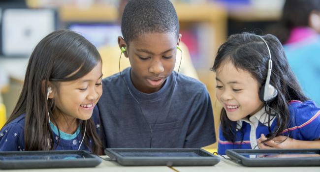 three children looking at a tablet while wearing headphones