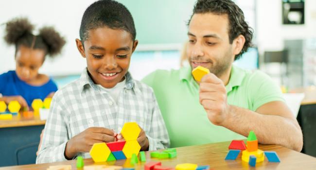 a man helpinga boy build something with shaped blocks